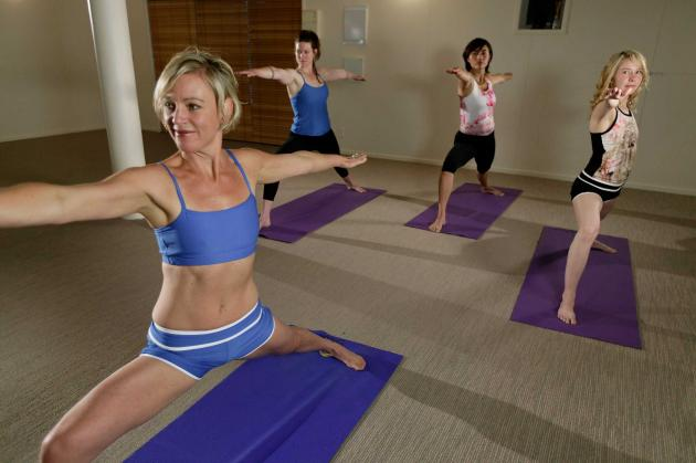 Peggy Preston leading students in her Bikram Yoga studio.